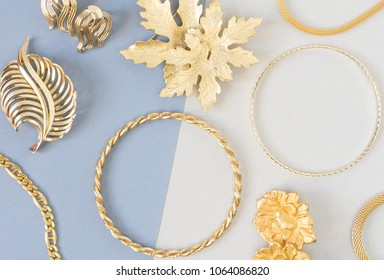 Woman's Jewelry. Vintage jewelry background. Beautiful gold tone brooches, braceletes, necklaces and earrings on blue background. Flat lay, top view