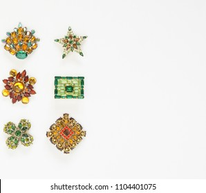 Woman's Jewelry. Vintage jewelry background. Beautiful bright rhinestone brooches on white. Flat lay, top view.