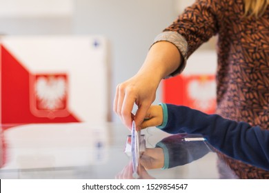 Woman's and kid's hands puting a card with a vote
