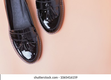 Woman's lacquered loafer shoes on the orange background, top view