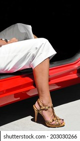 Woman's leg in high heel shoes getting out of a car