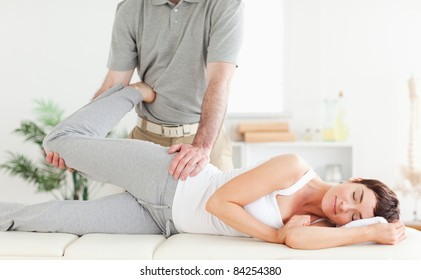 A woman's leg is stretched by a chiropractor