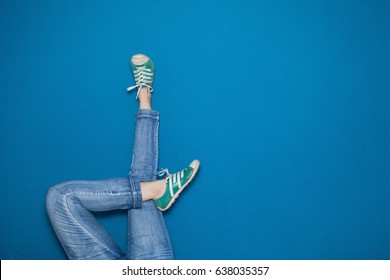 Woman's legs up against a wall in a relaxed pose