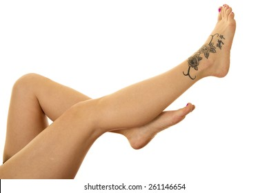 a woman's legs up in the air with her tattoo on her foot.