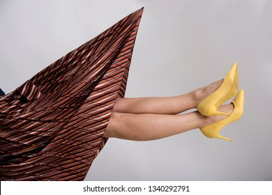 Woman's legs up in the air with yellow high heeled shoes. Beauty and fashion abstract conception.