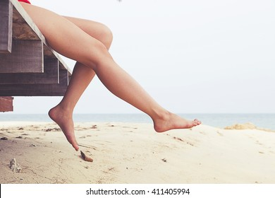 Woman's legs at beach jetty