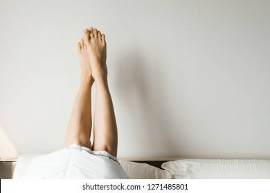 Woman's legs in bed on the white wall, resting or morning concept, selective focus