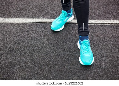 Woman's legs in blue colored running shoes standing on asphalt.