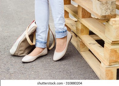 Woman's legs in blue jeans and white ballet flat shoes with beige bag, standing near wooden palettes