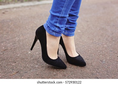 Woman's legs in blue skinny jeans and black leather suede high heels. Stylish elegant woman walking in the park.