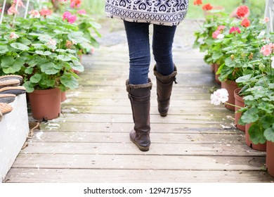 Woman's legs in boots walking along wooden path with potted flow