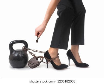 Woman's legs with chains and weights. The concept of business