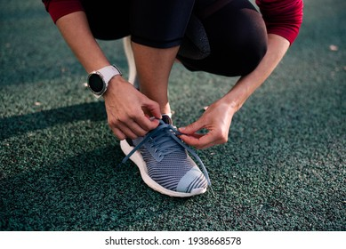 Woman's legs. Girl wear running shoes stand in stadium. Healthy exercise concept. On the start to run. Outdoor. Girl knots sneakers adidas and on hand wearing watch suunto.