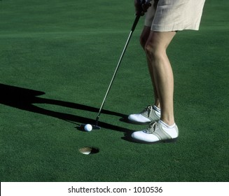 Woman's legs,  golfing on the green, woman putting ball.