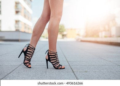 Woman's legs in high heels. Urban background.