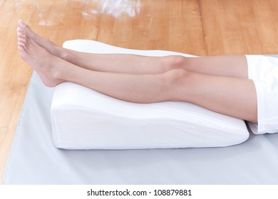 A woman's legs lay down on a pillow for relaxing and preventing varicose vein