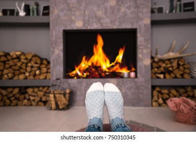 Woman's legs on the background of the fireplace