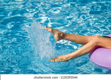 Womans legs on the inflatable ring playing with water in the swimming pool. Summer Vacation. Enjoying suntan. Weekend on resort