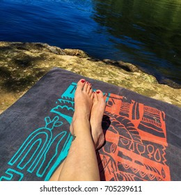 Woman's legs on towel at river.