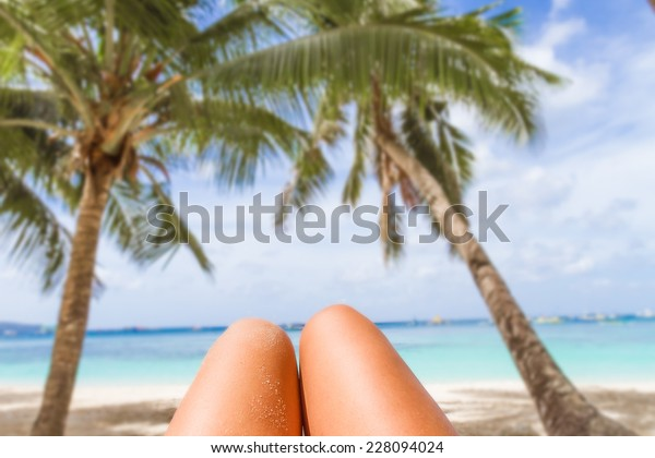 woman's legs on tropical beach and sea background, summer vacation