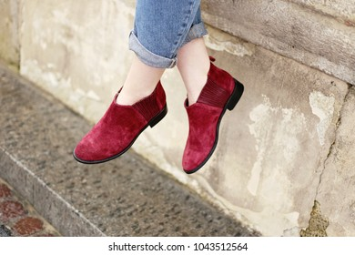 Woman's legs in purple suede low boots. Woman in wine red suede shoes on the city street. Shoes fashion trends