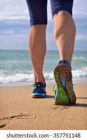 Woman's legs, runner's legs against ocean beach. Female running walking shoes of jogger outdoors. Shallow depth of field, focus on right foot.