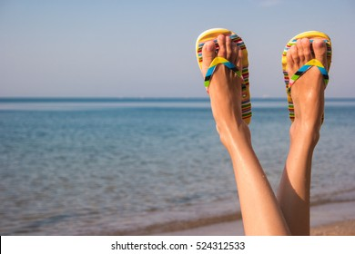 Woman's legs and sea. Feet wearing flip flops.