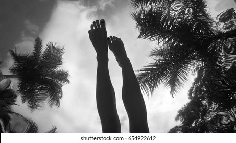 Woman's legs in the sky among palm trees - surrealistic shoot from underwater