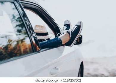 Woman's legs in sneakers in the window car with straw hat. Girl in jeans in the car with her legs crossed. Summer travel