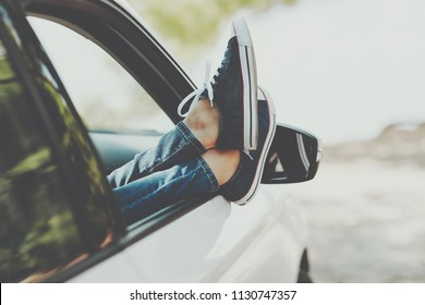 Woman's legs in sneakers in the window car. Girl in jeans in the car with her legs crossed. Summer travel