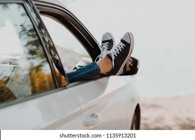 Woman's legs in sneakers in the window car with road map. Girl in jeans in the car with her legs crossed. Summer travel