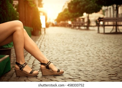 Woman's legs wearing black sandals outdoors