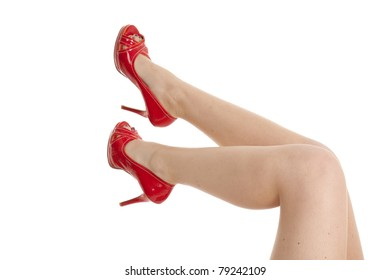 a woman's legs wearing red high heel shoes.