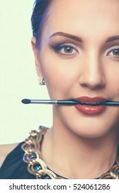Womans lips holding make up brush, isolated on white background