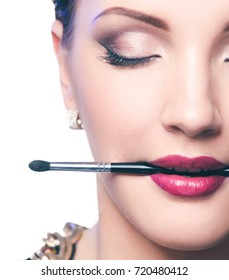 Woman's lips holding make up brush