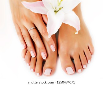 womans manicure pedicure with flower lily close up isolated on w