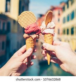 Woman's and man's hands holding italian ice cream in waffle cone on summer light.