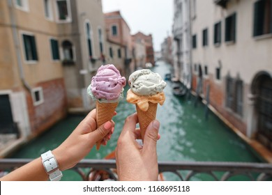 Woman's and man's hands holding italian ice cream in waffle cone on the backgound of italian city. Tasty italian gelato