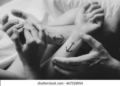 Woman's and man's hands with tattoo together