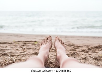 Woman's or men feet on the coarse sand near the sea. Relaxation at sea in countries with cold climates. Beach vacation holidays concept of freedom and travel. Close-up. Copy space. Travel lifestyle.