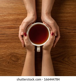 Womans and mens hands holding hot cup of tea on wooden table