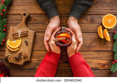 Womans and mens hands holding hot  glass mug. Christmas hot drink - mulled red wine with spices and fruits in the hands of men and women. New Year decoration on a wooden background. Top view