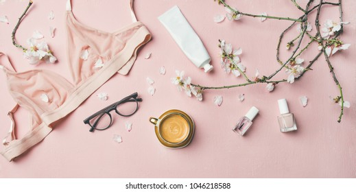 Womans morning rituals concept. Flat-lay of feminine tender powder color lingerie, glasses, cosmetic items, cup of coffee and Spring blossom flowers over pastel pink bed cover, top view.