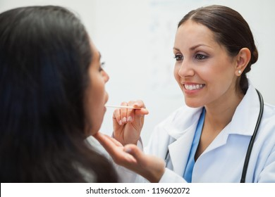 Womans mouth being examined by happy doctor in hospital room