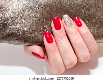 Woman's nails with beautiful red manicure fashion design with gems