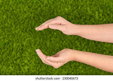 Woman's open hands making a protection gesture isolated on green background.