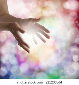 Woman's outstretched healing hands with light bokeh background and ball of white energy between