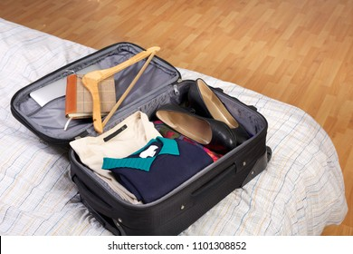Woman's packed open black suitcase on top of a bed
