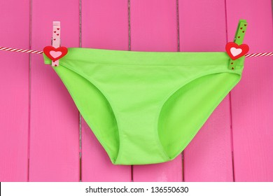 Womans panties hanging on a clothesline, on pink wooden background