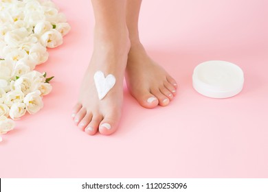 Woman's perfect, groomed feet with jar of natural herbal cream. Care about clean, soft and smooth skin. Heart shape created from cream. Love a body. Beautiful roses on pink background. Fresh flowers.